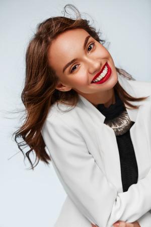 dientes sanos: Hermosa mujer joven sonriente con una perfecta sonrisa y dientes blancos sanos en en el estudio y mirando a la cámara. Fondo blanco. Retrato Foto de archivo