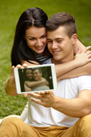 using tablet: Couple Using Digital Tablet and Smiling While Sitting Close To Each Other Stock Photo
