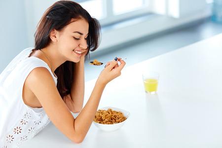 comiendo cereal: Mujer joven hermosa con una cuchara en la mano y un plato de cereal mirando hacia abajo y sonriendo. Desayuno saludable en la mañana.