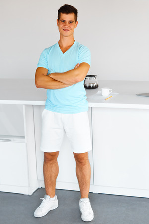 young man portrait: Full length portrait of a young charming man standing and smiling at the camera  in the kitchen