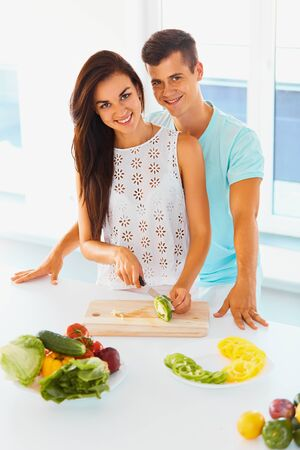 a young family: Smiling young couple preparing dinner and smiling at the camera. Woman is cutting sweet pepper with a knife , man is hugging her from behind. Healthy vegetarian family. Stock Photo