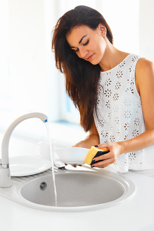 apartment cleaning: Beautiful smiling young woman doing the washing up in modern white .kitchen Stock Photo