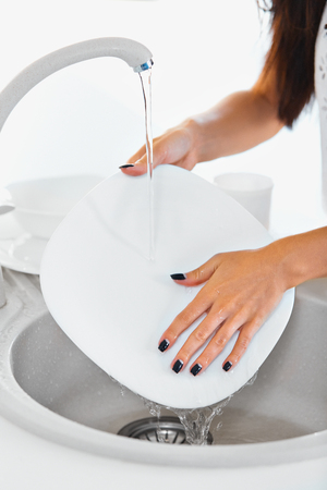 scrubbing up: Young woman hands with nice manicure washing dishes in the sink in the kitchen. Close up view. Stock Photo