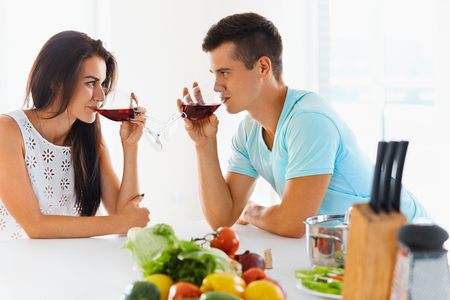 tomando vino: Happy couple looking at each other with love while drinking red wine in kitchen at home
