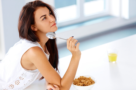 young beautiful woman: Wellness concept. Beautiful young woman eating organic cereal and smiling. Healthy breakfast in the morning. Dieting concept. Stock Photo
