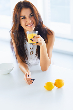 people: Healthy breakfast. Attractive cheerful young woman drinking orange juice in her kitchen and smiling at the camera. Wellness concept Stock Photo