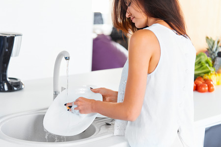 Bella gara giovane donna che fa il lavaggio-up in cucina bianca sorridente. Vista dalla parte posteriore. Archivio Fotografico - 46287108