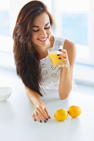summer diet: Tasty healthy breakfast. Beautiful young brunette woman drinking orange juice and smiling.