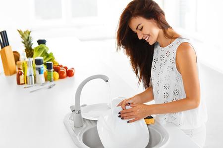 lavar trastes: Ama de casa joven feliz que está haciendo el lavavajillas después de la cena vegetariana. Vehículos en el fondo.