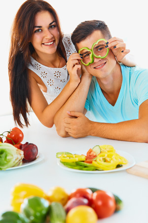 eyes: Vegetables are fun. Young  smiling woman is holding slices of bell pepper  in front of eyes of her boyfriend. Young attractive couple  having fun while cooking dinner. Healthy eating