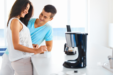 Young smiling woman making black coffee for her husband in the kitchen in the morning .