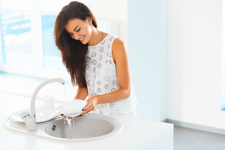 Beautiful smiling young woman doing the washing up in modern white kitchen Banco de Imagens - 46287211