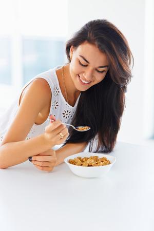 cuchara: desayuno saludable en la mañana. Hermosa mujer joven con una cuchara en la mano y un plato de cereal mirando hacia abajo y sonriendo.