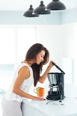 Beautiful young woman making coffee for breakfast using filter coffee machine in the kitchen. She lifts the lid.