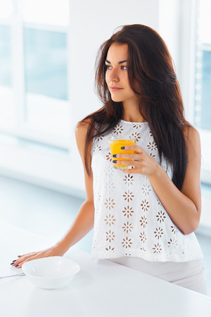 looking aside: Young beautiful caucasian woman drinking orange juice smiling and looking aside