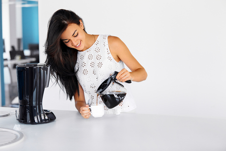 women holding cup: Photo of a woman on her break pouring herself a mug of hot filtered coffee from a glass pot