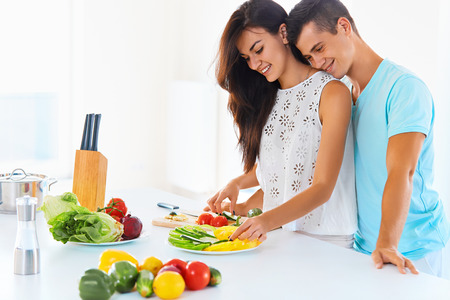 Smiling young couple preparing dinner .  Woman is cutting vegetables with a knife , man embracing her from behind. Healthy vegetarian family.