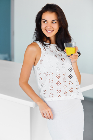 happieness: Beautiful young woman drinking fresh orange juice in the kitchen. Happiness, wellness concept.