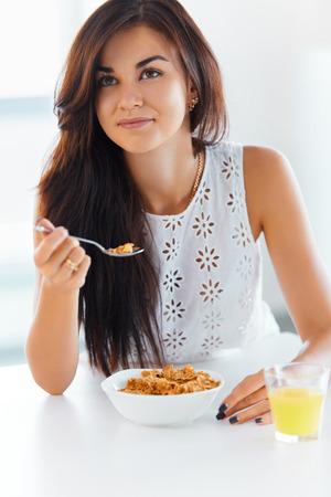 comiendo: Retrato de la hermosa mujer comiendo cereales jóvenes. Alimentación saludable. Cuidado de la salud.