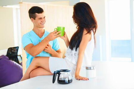 mujeres juntas: Hombre hermoso joven dando hermosa mujer una taza de caf� negro caliente, mientras ella est� sentada en la encimera de la cocina.