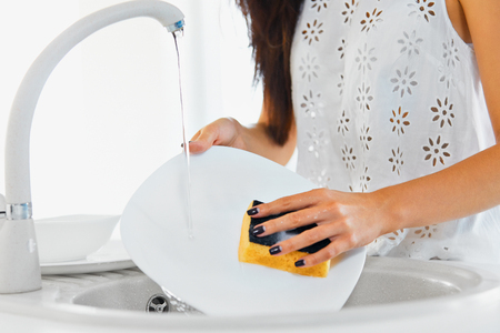 Young woman hands with nice manicure washing dishes in the sink in the kitchen using sponge with soap foam. Close up view.