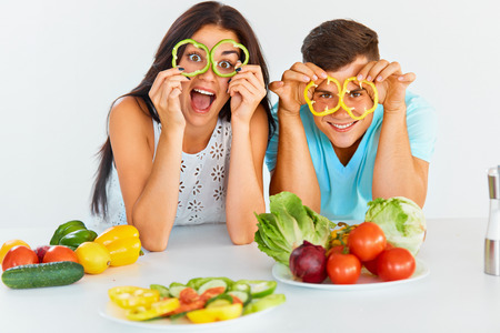 vegetables young couple: Young, smiling couple is holding slices of bell pepper in front of their eyes smiling at the camera