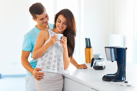 若い魅力的な女性の飲むコーヒー、男性の台所で後ろから彼女を抱いて笑顔