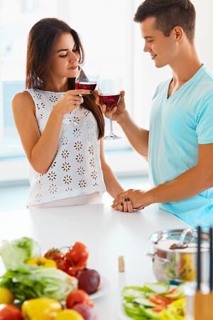 clinking: Happy smiling couple clinking their glasses of red wine smiling and drinking their drinks Stock Photo