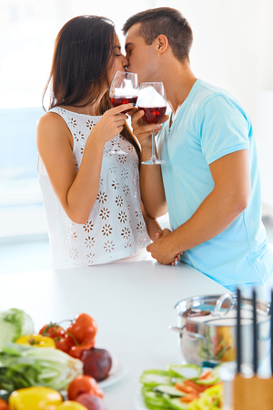 lovely couple: Young handsome man and beautiful woman with red wine kissing in the kitchen Stock Photo