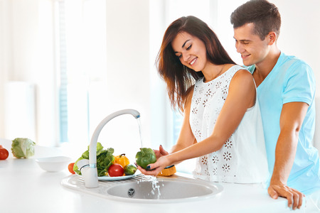 Happy young beautiful woman washing vegetables while handsome man hugging her from behind in kitchen.