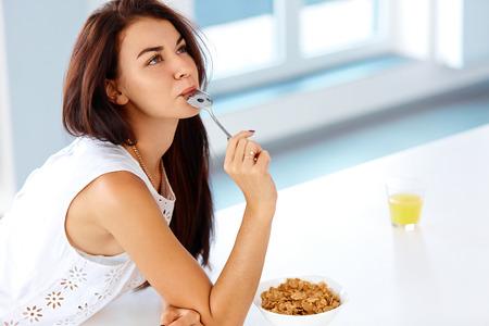 colazione: Concetto di benessere. Bella giovane donna con prima colazione e sorridente. Mangiare sano. Concetto di dieta.