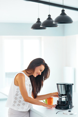 Beautiful smiling girl making coffee for breakfast using filter coffee machine in the kitchen 스톡 콘텐츠
