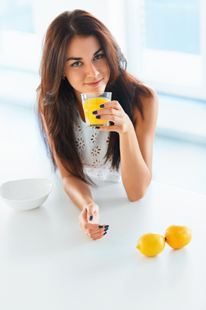 tomando jugo: Beautiful cheerful girl drinking orange juice in her kitchen and smiling at the camera. Citrus juice for health.