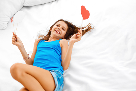 beautiful teen: Beautiful teenage girl lying on the bed , dreaming about love while holding paper hearts in her hands. Teenage love. Stock Photo