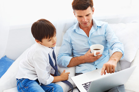 single father: Handsome single father drinking coffee and teaching son how to use notebook.