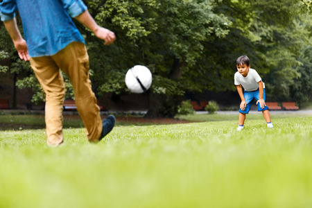 activity adult: A man and a boy playing football on the green grass in the park. Boy is very excited.