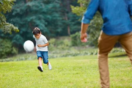 family playing: Summer football. Dad and son playing soccer on a green grass in the park. Family weekend. Stock Photo