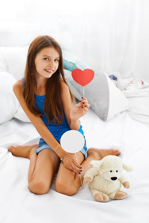 beautiful teen: Beautiful smiling teenage girl sitting next to  her teddy bear and holding white sign and red heart.