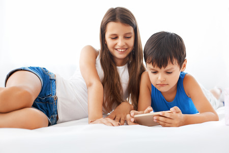 brothers: Teenage sister and her brother spending time together. They are using mobile phone while lying on the bed. Family leisure.