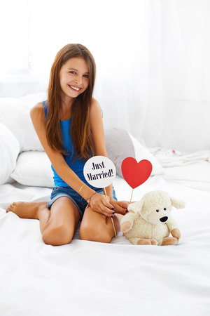 plush toy: Beautiful smiling teenage girl sitting next to her teddy bear and holding just married sign and red heart. Stock Photo