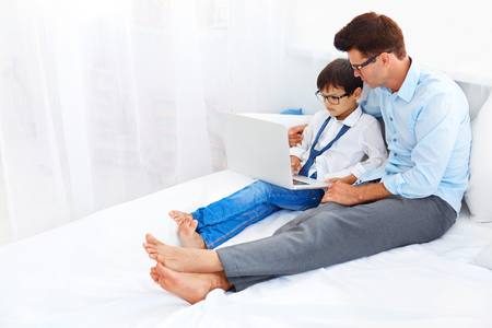 Handsome father and his cute son wearing stylish eyeglasses are using notebook in a bedroom. Archivio Fotografico
