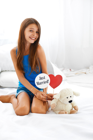 knees: Beautiful smiling teenage girl sitting next to her teddy bear and holding just married sign and red heart. Stock Photo