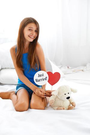 de rodillas: Hermosa sonriente adolescente sentado al lado de su oso de peluche y la celebración de firmar acaba de casarse y el corazón rojo.