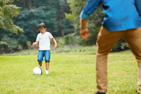 dad son: Summer football. Dad and son playing soccer on a green grass in the park. Family weekend. Stock Photo