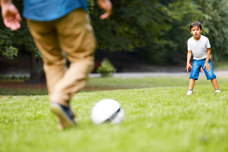 adult child: Father with his son playing football on the green grass in the park. Boy is very excited. Stock Photo