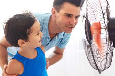Handsome father and  cute son cooling in front of fan. Hot summer day.
