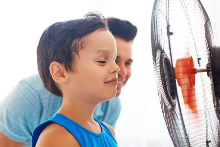 冷却ファンの前で彼の父を持つ少年。