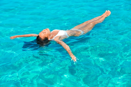 float: Young beautiful girl relaxing while floating in the sea.