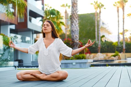 Morning meditation. Healthy woman sitting in lotus posture outdoors in spa and resort hotel. Stock Photo