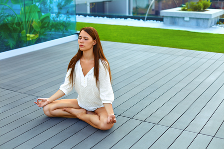 closed club: Young beautiful woman meditating outdoors in lotus posture. Healthy, vegetarian lifestyle.